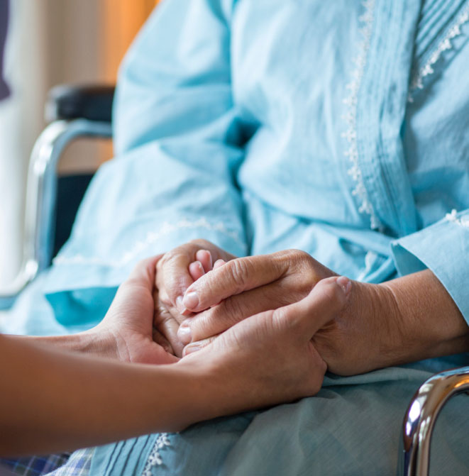 Holding hands of patient in wheelchair